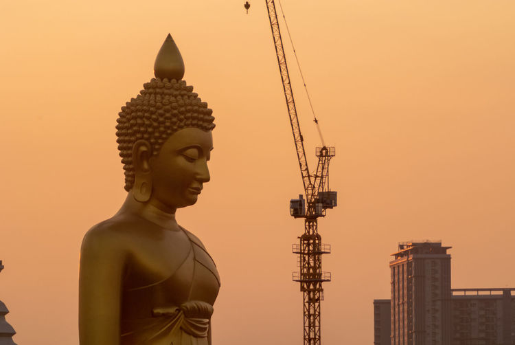 Low angle view of statue against building against sky during sunset