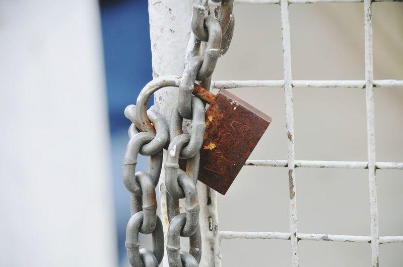 Close-up of rusty padlock hanging on metal