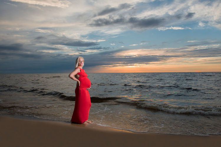 Portrait of pregnant woman standing on shore at beach during sunset