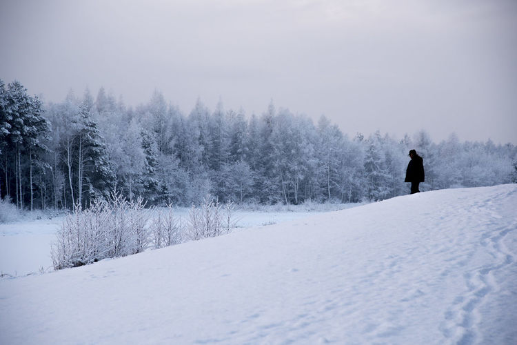 Man On Snow Covered Landscape Against Sky