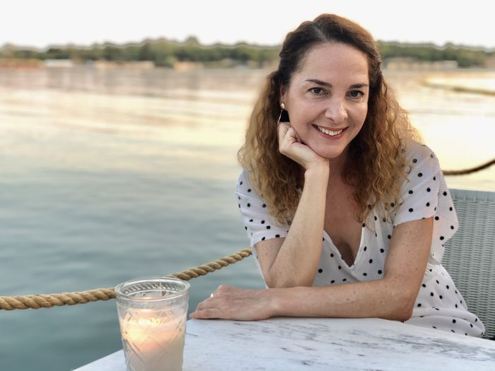 Portrait of a smiling woman sitting next to sea in a coffee shop at sunset,
