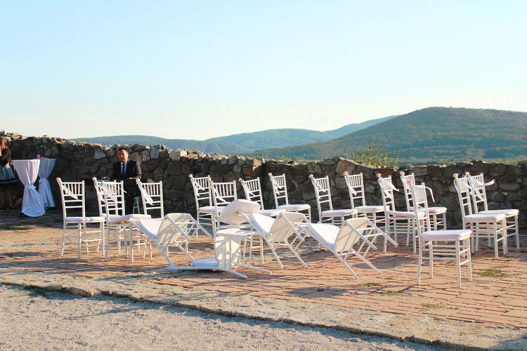 Empty Chairs Lonely Stool Absence After Ceremony Chair Clear Sky Day Mountain Range No People Outdoors Seat Seats Sky Solitude Sunlight Table Tranquil Scene Tranquility Wedding Day White Chairs