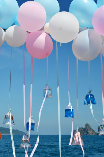 Helium Balloons Flying With Liquids In Plastic Bags Against Sea
