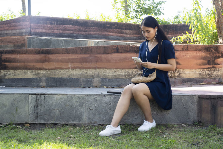 Full length portrait of young woman sitting on mobile phone