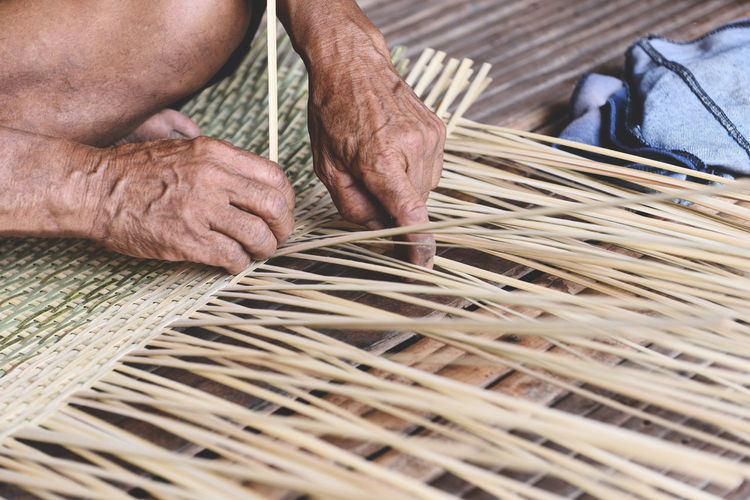 High angle view of craftsperson weaving straw basket