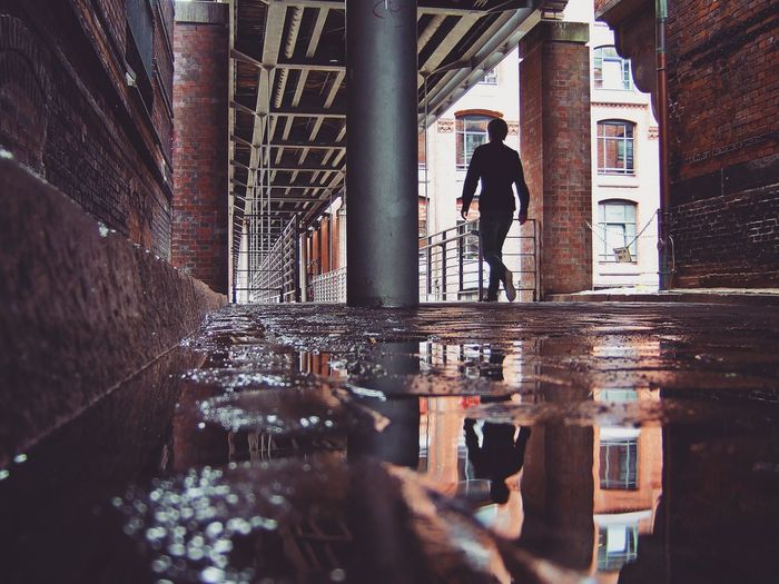 Rear view full length of man reflecting on puddle at corridor in building