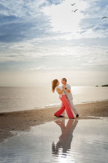 Mature couple dancing at beach against sky
