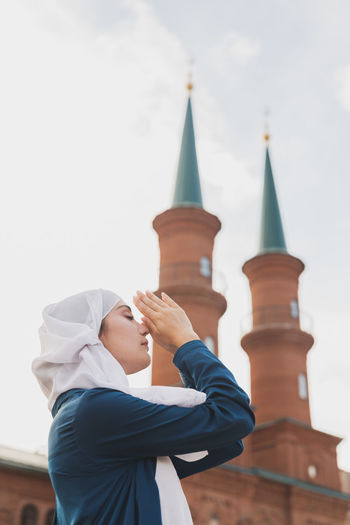 Side view of woman praying against mosque