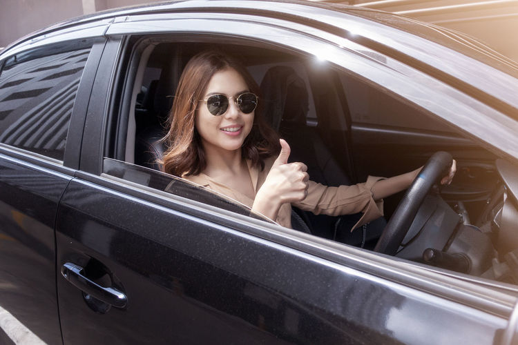 Portrait Of Smiling Young Woman Gesturing While Driving Car