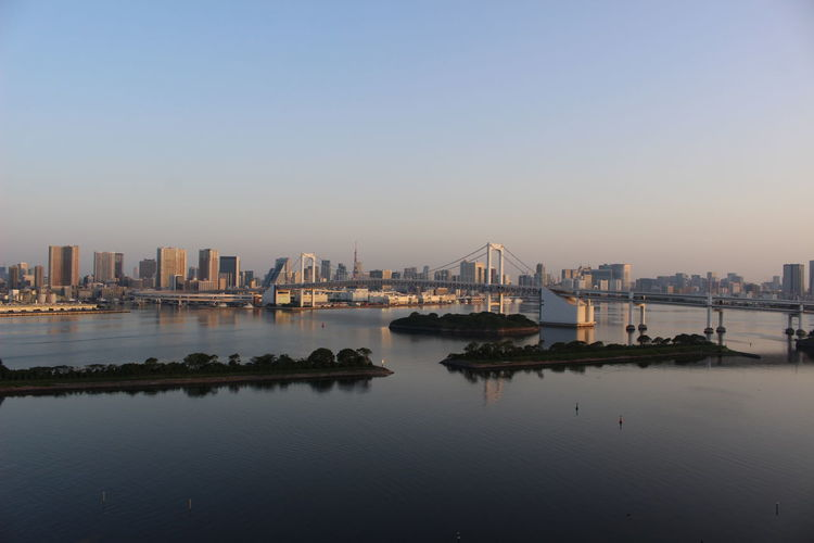 City by river against clear sky