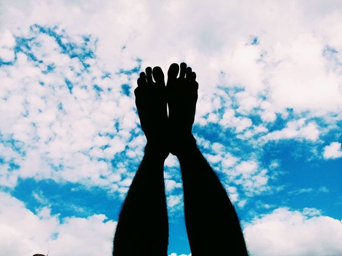Low section of silhouette person with feet up against cloudy sky