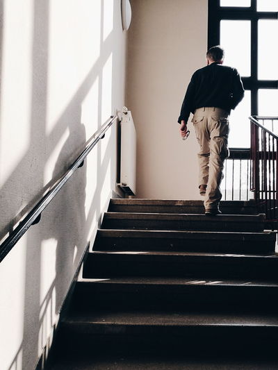 Full length rear view of man walking on stairs at home