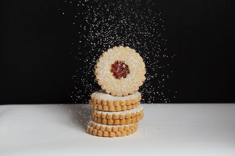 Sprinkling sugar on freshly baked homemade cookies Food And Drink Food Studio Shot Black Background Indoors  Sweet Food Freshness Still Life Close-up No People Indulgence Sugar Baked Ready-to-eat Copy Space Unhealthy Eating Table Powdered Sugar Sweet Black Color Temptation Snack Homemade Freshness Jam Freshly Baked Freshly Cookies Cookie