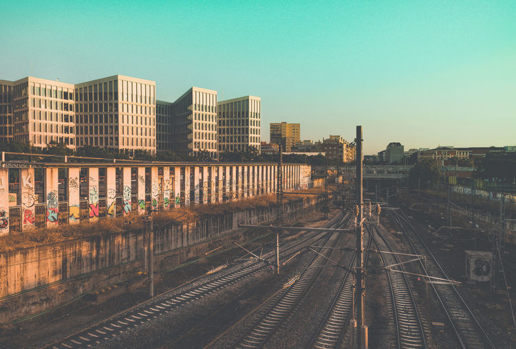a railway track with nice buildings at the end and a cool sunset Architecture Building Exterior Built Structure City Clear Sky Day No People Outdoors Public Transportation Rail Transportation Railroad Track Railway Track Sky Transportation