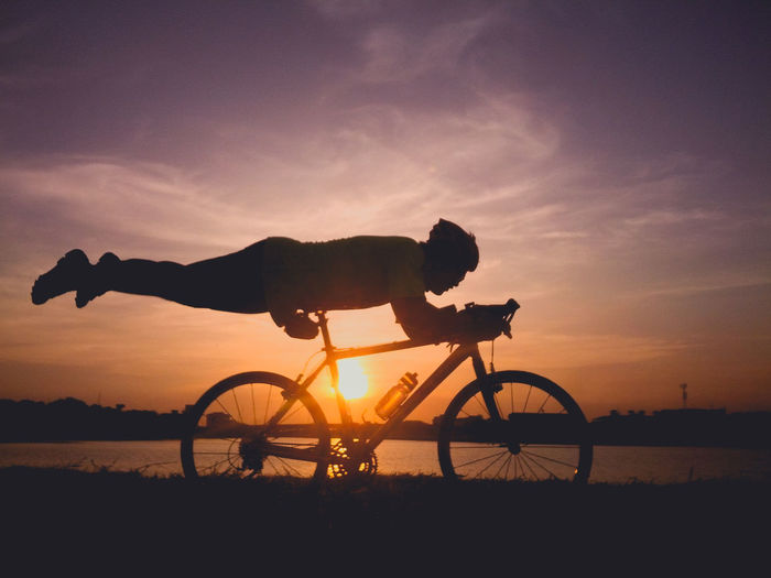 Silhouette man balancing on bicycle seat by lake against sky during sunset