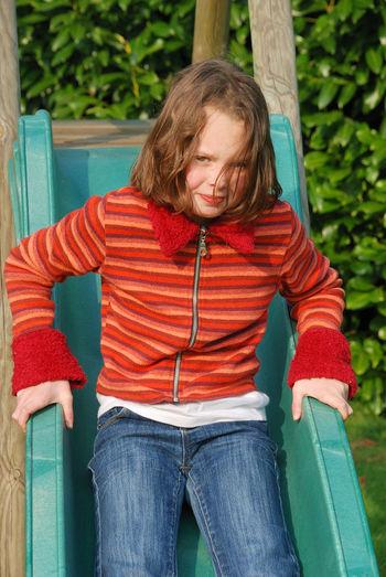 Portrait of cute girl sliding at park