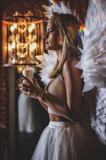 Prayer Wings Angel Wings Candles Chirch Ritual One Person Real People Women Side View Waist Up Looking Illuminated Focus On Foreground Young Adult Three Quarter Length Blond Hair