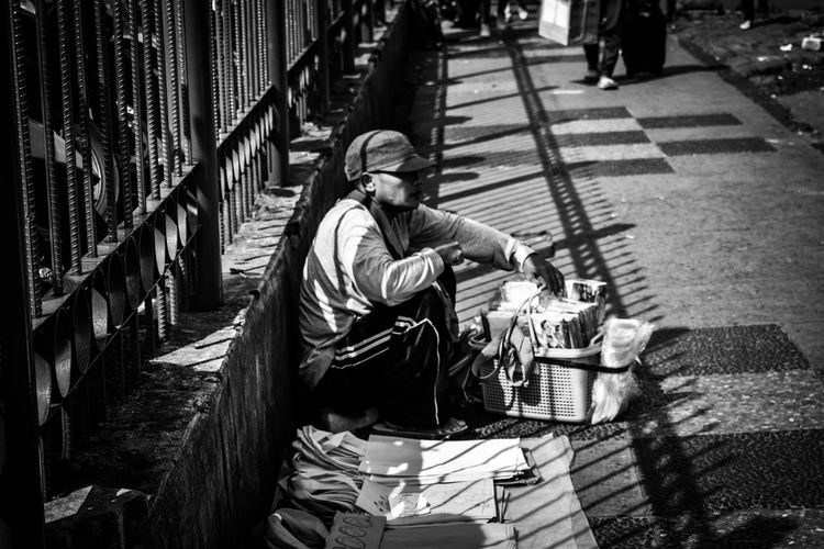 Side view of man selling books and bags on footpath