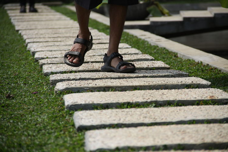 Low section of man walking on stepping stone