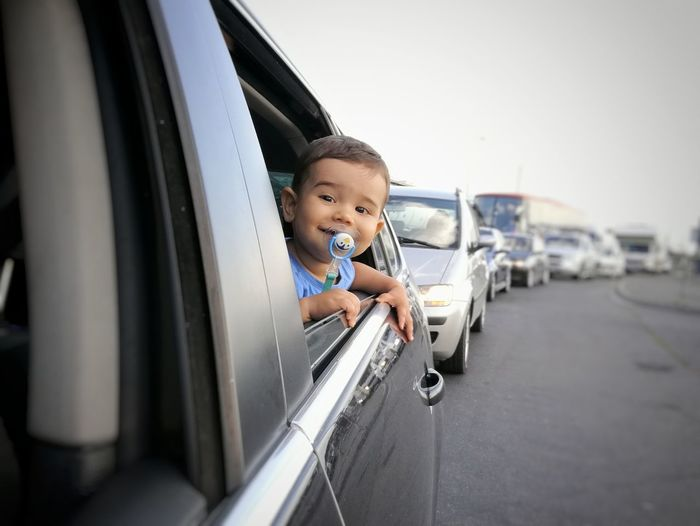 Small child looking through an open car window Child Childhood Looking At Camera Smiling Baby Boy Car Window Roadtrip Boy On Car Transportation Traveling Traffic Jam Toddler  Happy Child  Happiness Through Car Window Road On The Road Family Trip Lifestyle People Baby In Car Vehicle The Week On EyeEm