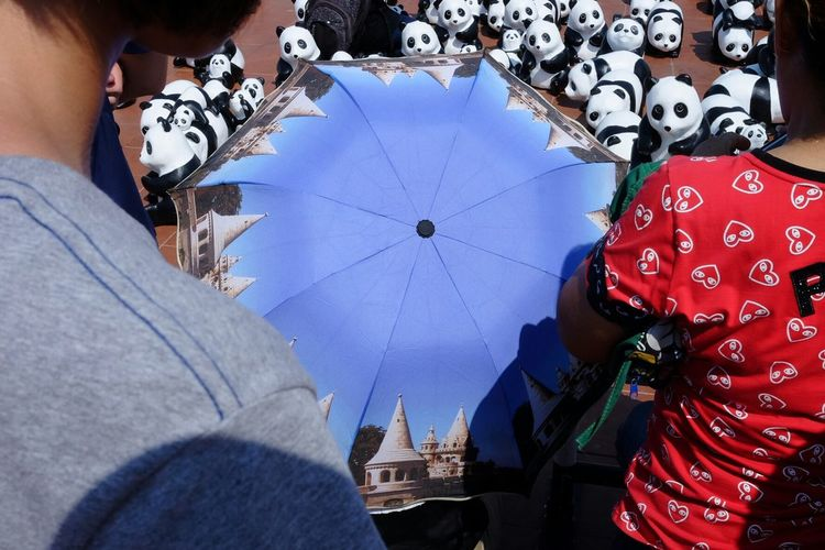 Cropped Image Of People With Umbrella And Toy Pandas