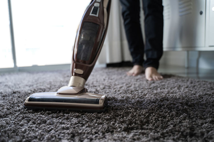 Low Section Of Person Cleaning Rug With Vacuum Cleaner At Home