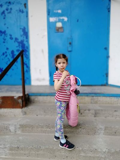 Full length of cute girl eating candy while standing on steps