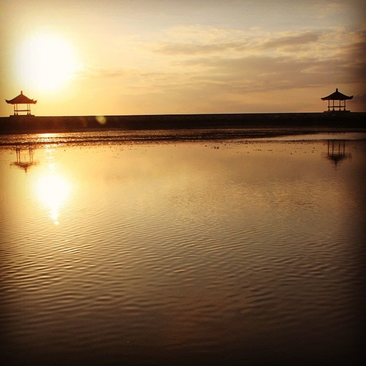 sunset, water, sea, reflection, sky, tranquility, nature, architecture, silhouette, scenics, beauty in nature, tranquil scene, cloud - sky, built structure, beach, travel destinations, outdoors, building exterior, no people, horizon over water, day