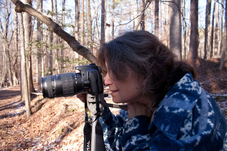 Side view of woman photographing with digital camera in forest