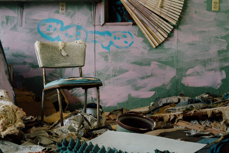 Close-up of abandoned chair in messy area