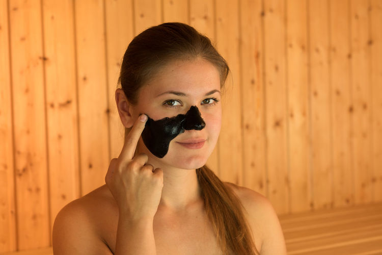 Portrait of beautiful young woman applying facial mask on face while sitting in sauna