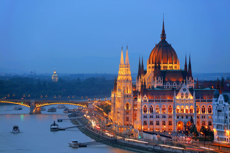 Bridge Over River By Illuminated Hungarian Parliament Building Against Sky In City At Dusk
