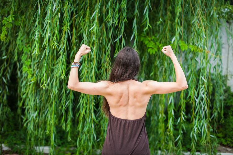 Rear view of woman flexing muscles while standing against plants