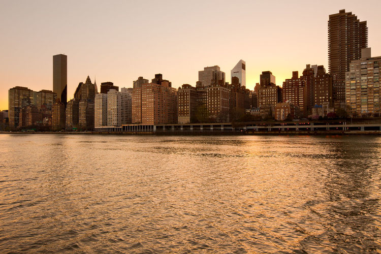 Skyline of midtown Manhattan at sunset, New York City, NY, USA Apartment Buildings Architecture City Cityscape East River Manhattan Murray Hill New York City Skyline USA Buildings Dusk Midtown Neighborhood Residential District River Silohuette Sunset Turtle Bay Waterfront