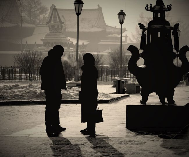 Silhouette People Standing On Footpath By Sculpture During Winter