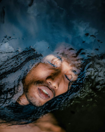 Portrait of young man with reflection in water