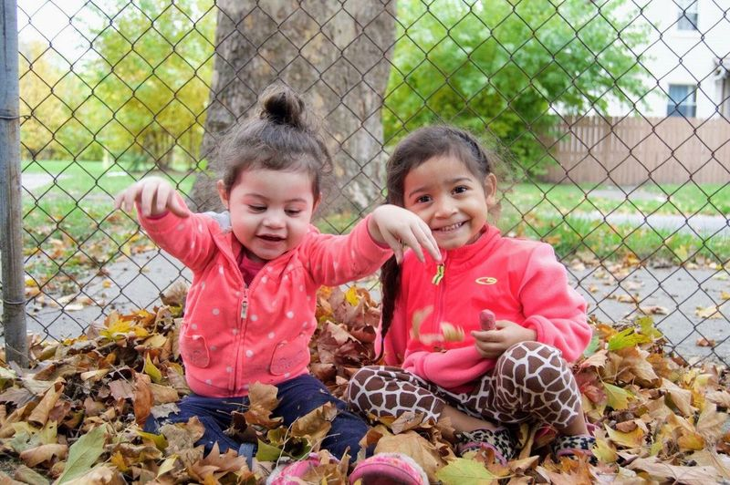 Happiness Fence Smiling Togetherness Bonding Childhood Child Cheerful Looking At Camera Playing Beginnings Detroit Innocence Sitting Sisters