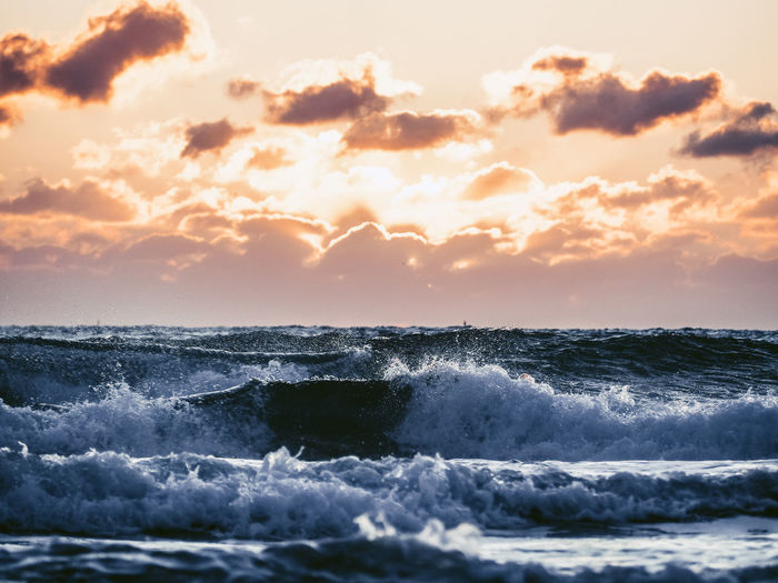 Sea waves rushing towards shore against sky during sunset