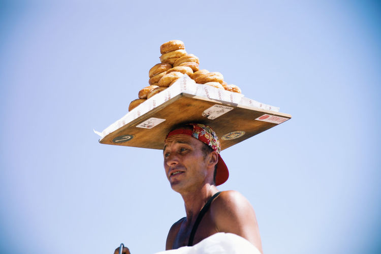 Man balancing tray of bread against clear sky