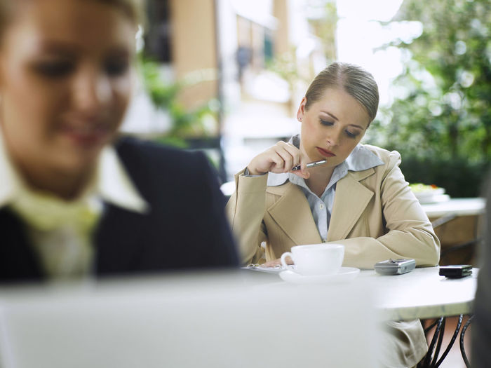 Close-Up Of Businesswoman With Colleague Sitting In Background At Cafe