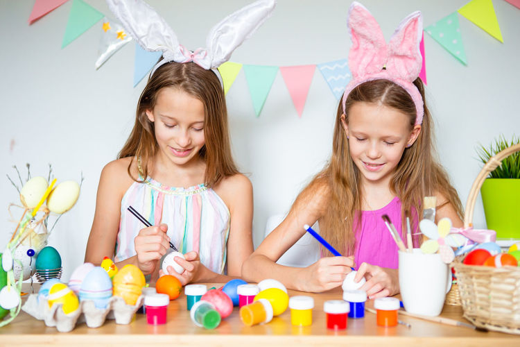 Cheerful girls painting eggs at home