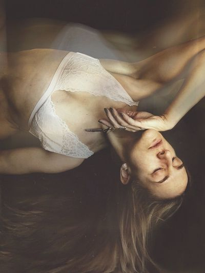 High Angle View Of Sensuous Woman Wearing Bra Lying On Bed At Home