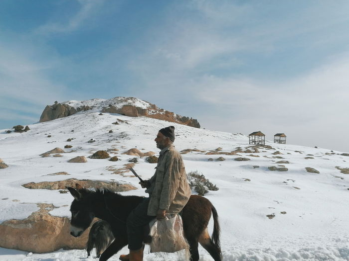 Person riding horse on snow covered mountain against sky
