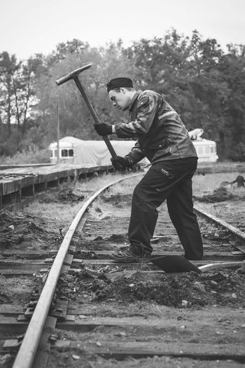 Side view of man working on railroad track
