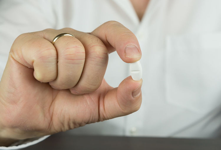 Cropped hand of businessman holding medicine at desk in office