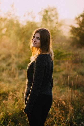 Portrait Of Young Woman Standing On Field During Sunset
