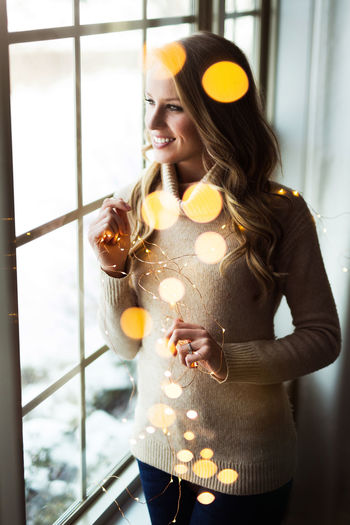 Christmas Christmas Lights Adult Adults Only Beautiful Woman Day Holding Indoors  Leisure Activity Lifestyles Long Hair One Person One Woman Only One Young Woman Only People Real People Smiling Standing Window Windows Women Young Adult Young Women