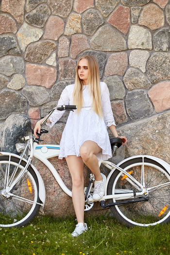 Full length of woman with bicycle in background