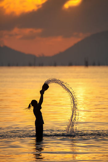Children playing in the lake. Arms Raised Beauty In Nature Cloud - Sky Human Arm Lake Leisure Activity Lifestyles Mountain Nature One Person Orange Color Outdoors Real People Reflection Scenics - Nature Silhouette Sky Standing Sunset Water Waterfront EyeEmNewHere