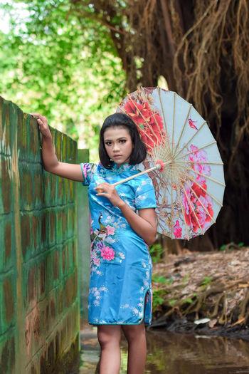Full length portrait of smiling girl standing against wall